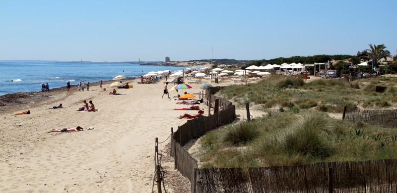 Playa de Es Cavallet con la Torre de Ses Portes al fondo.